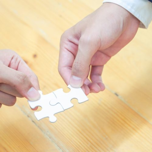 Close-up view of businesspeople solving jigsaw puzzle represent team work and cooperation